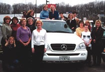 Arbonne sales consultants work their way to a white Mercedes